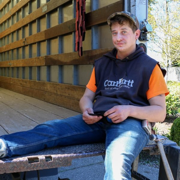 Second Use Employee Dash takes a break on the edge of the bed of a truck on a job site.